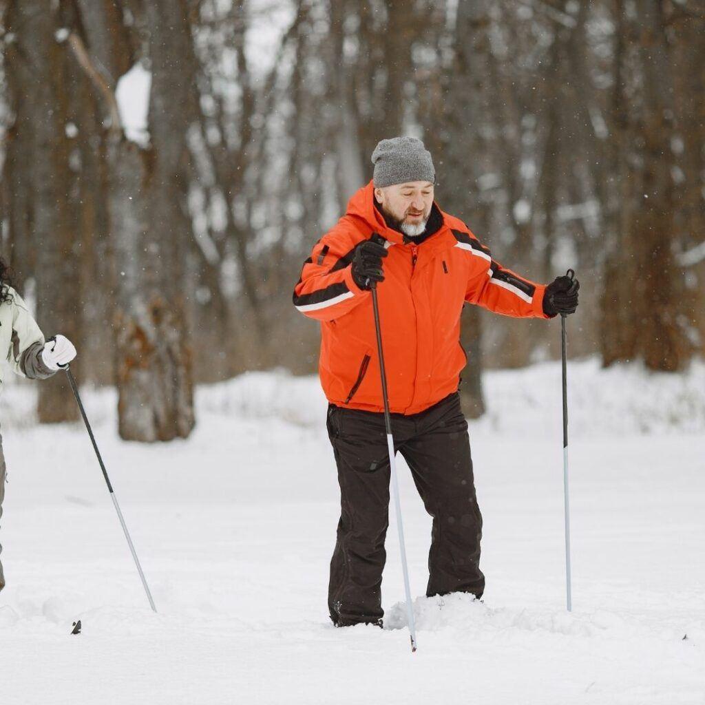 elderly man trekking through the snow